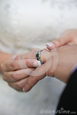 Bride putting on wedding ring