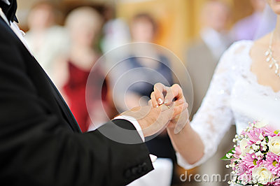 Bride putting a wedding ring on groom s finger