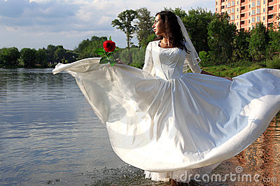 Bride with red rose at pond