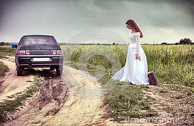 Bride on the rural road with an old suitcase