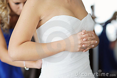 Bride s hands while putting wedding dress