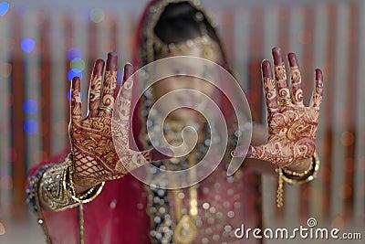 Bride showing henna on her hands hands in Indian Hindu wedding