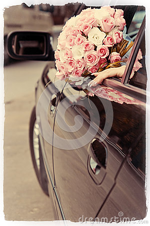 Bride shows wedding bouquet from window of car