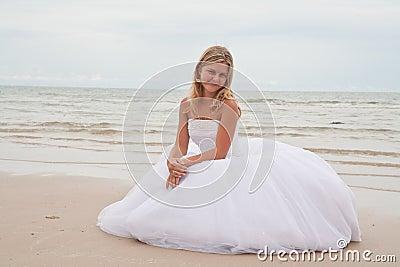 Bride sitting on a beach