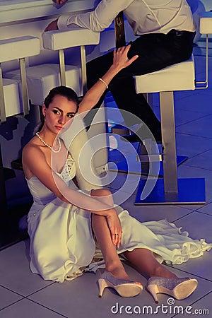 Bride sitting on floor next to bar