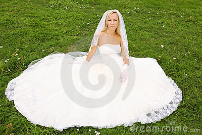 Bride sitting on green grass