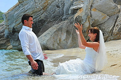 Bride splashing groom with sea water