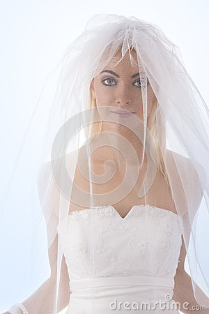 Bride with veil on the face in front of the camera
