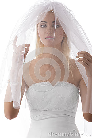 Bride with veil on the face looks in to the lens