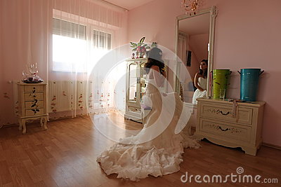 Bride watching in the mirror preparing for her wedding