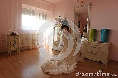 Bride watching in the mirror preparing for her wedding