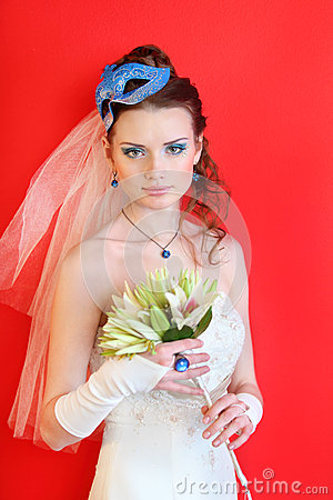 Bride wearing dress with blue mask in hairdo
