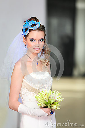 Bride wearing in dress with mask in hairdo