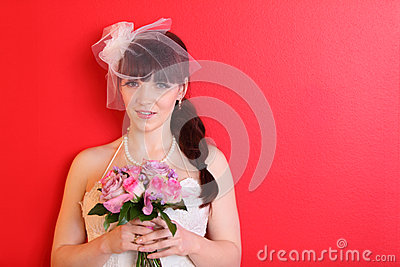 Bride wearing dress and short veil holds bouquet