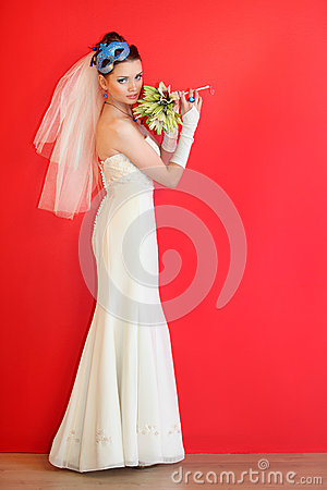 Bride wearing white dress with blue mask in hairdo