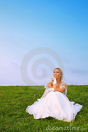 Bride wearing white dress sitting on grass