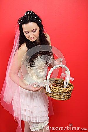 Bride wearing in white short dress holds basket