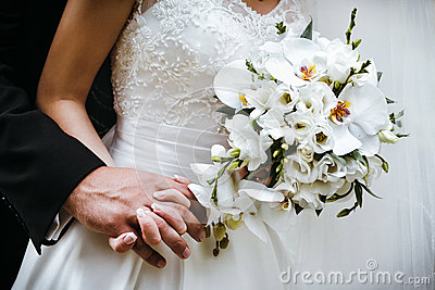 Bride with wedding bouquet of white orchids and groom holding ea
