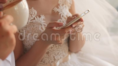 Bride in wedding dress holding smartphone in hands. Groom is drinking cappuccino. Closeup shot stock video footage