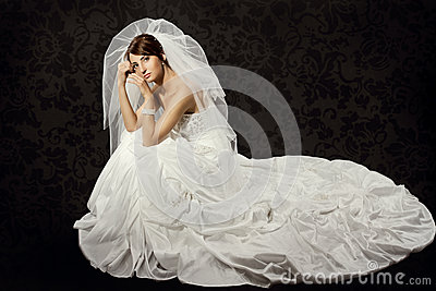 Bride in wedding dress over dark background