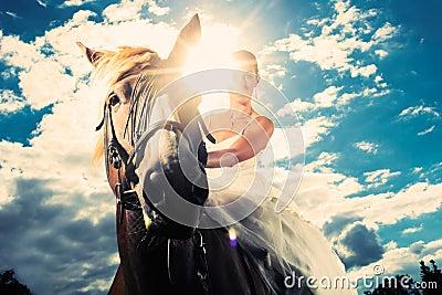 Bride in wedding dress riding a horse, backlit