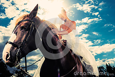 Bride in wedding dress riding a horse, backlit