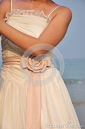 Bride in wedding dress under sunset in the beach