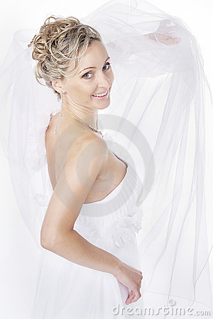 Bride in white veil looking at camera and smiling.