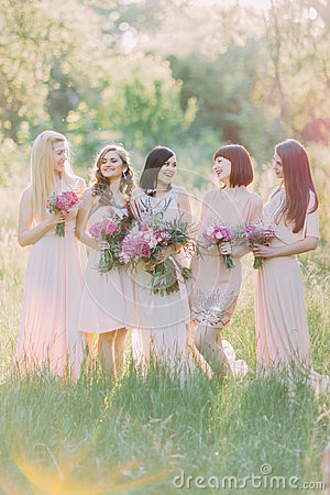 Free Bride With Her Bridesmaids Are Laughting And Holding The Bouquets Of The Pink Flowers In The Green Sunny Forest. Royalty Free Stock Image - 98571676