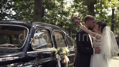 Bridegroom hugs and kisses his wife. Lucky bridegroom hugs and kisses his wife at a walk in the park near a rented retro car stock footage