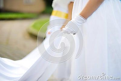 Bridesmaids holding bride s wedding dress