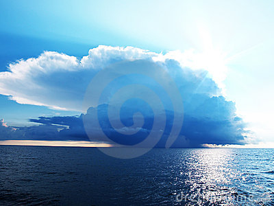 Bright blue sky with stormy clouds over a sea