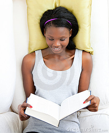 Bright female teenager reading a book on a sofa