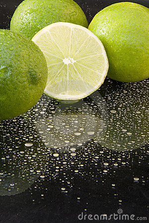Bright fresh green limes on dark background