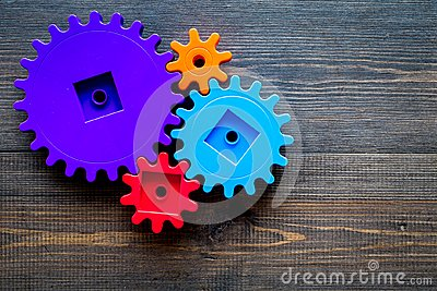 Bright gears for great technology of team work and correct mechanism on wooden background top view copyspace Stock Photo