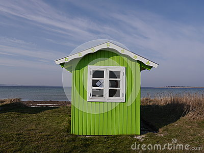 Bright green beach hut on Danish island of Aeroe with background of sea and blue sk