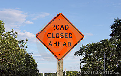 Bright orange road closed ahead sign