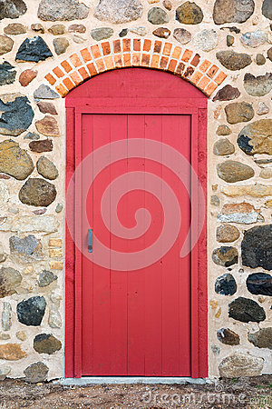 Free Bright Red Arched Door In A Stone Wall Royalty Free Stock Image - 61077676