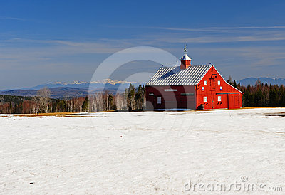 Bright red barn and snow covered field