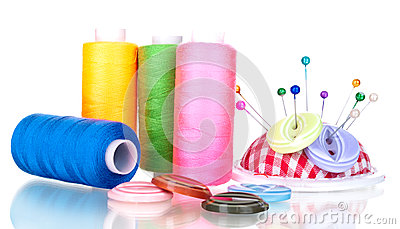 Bright sewing buttons, needle and skeins of thread