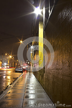 Bright Wet City Sidewalk and Street At Night