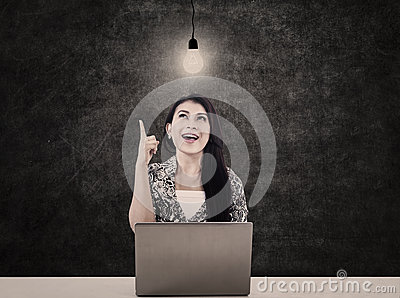 Bright woman with laptop and lit bulb