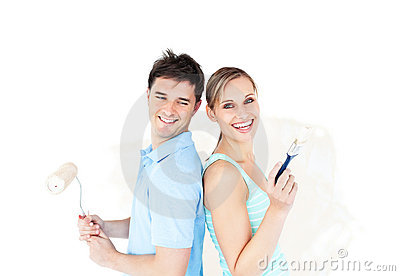 Bright young couple painting a room