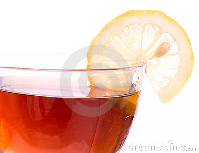 Brim of transparent cup with tea and lemon