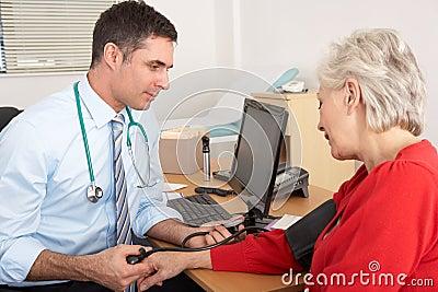 BRITISCHER Doktor, der Blutdruck der älteren Frau nimmt