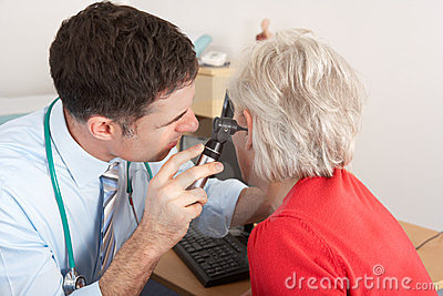 British doctor examining senior woman s ear