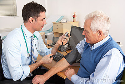 British doctor taking senior man s blood pressure