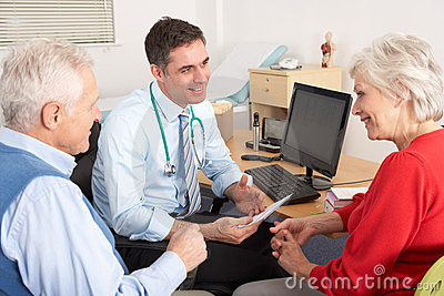 British GP talking to senior couple in surgery