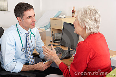 British GP talking to senior woman in surgery