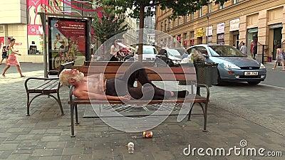 BRNO, RÉPUBLIQUE TCHÈQUE, LE 11 AOÛT 2015 : Homme sans abri d'émotion authentique endormi sur un banc banque de vidéos